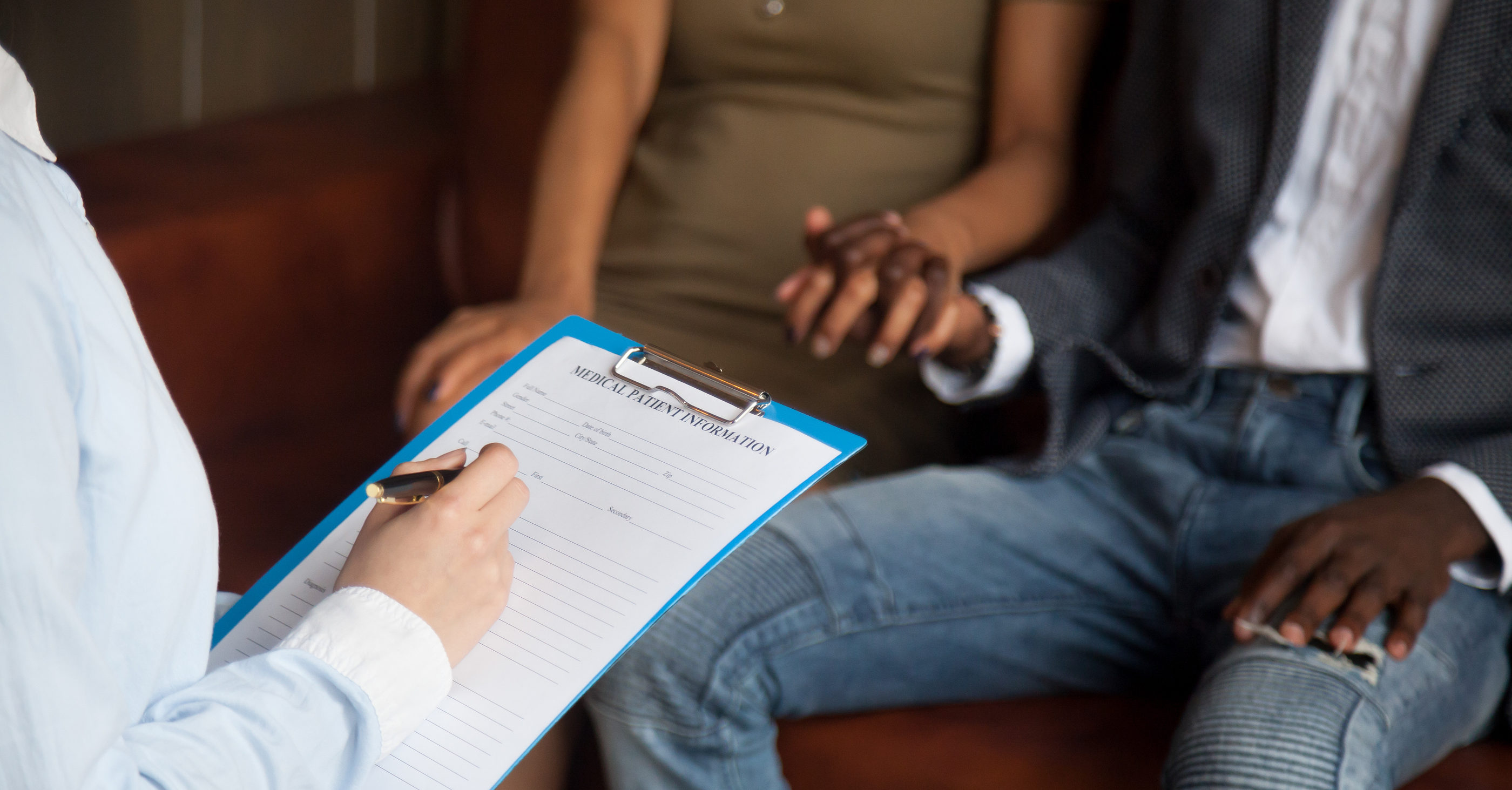 Doctor or psychologist filling medical patient information form holding clipboard consulting african american couple, marriage counseling, family therapy, fertility treatment for infertility concept