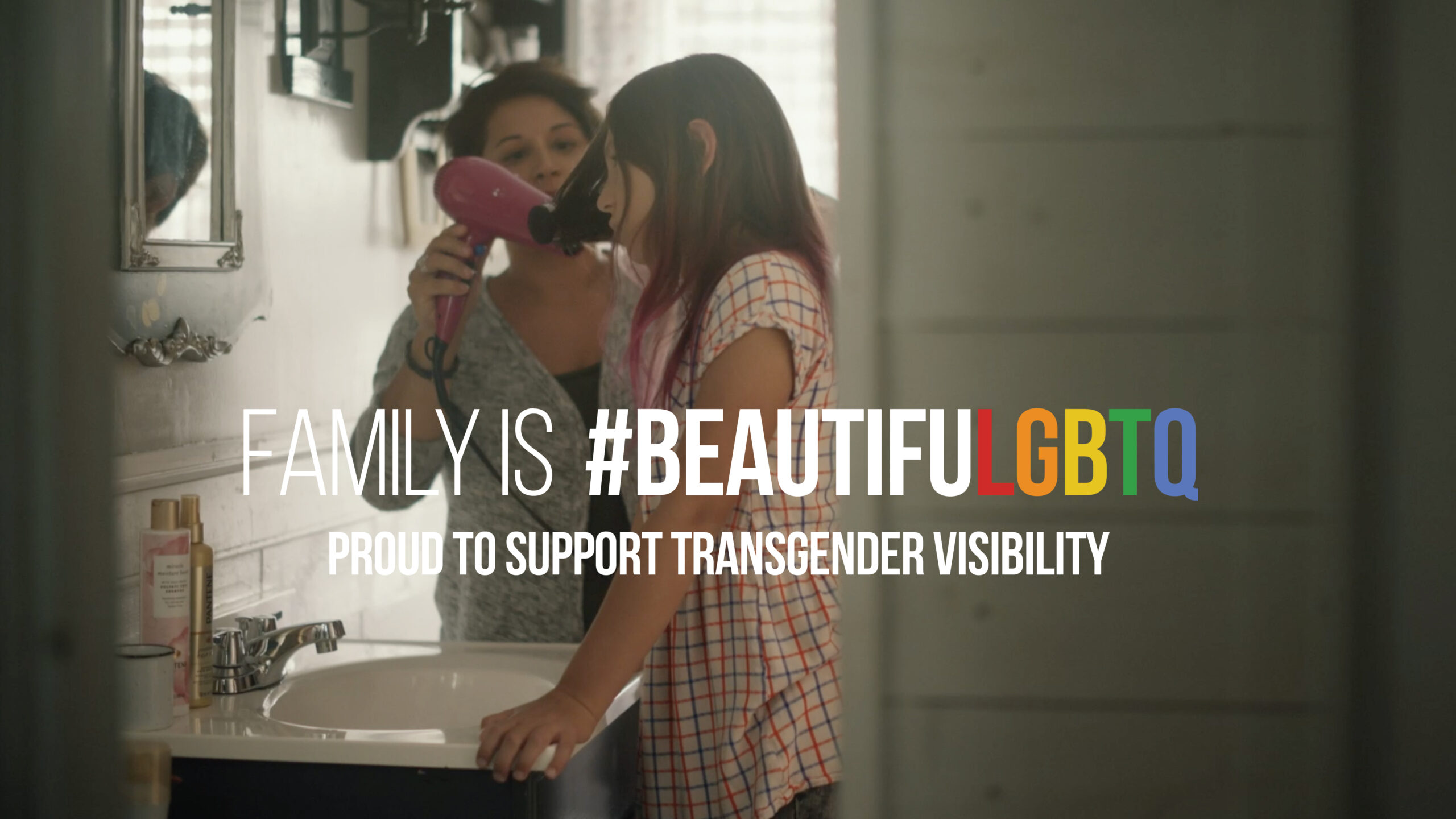 """Mom drying daughters hair with text that reads, """"Family Is #BeautifuLGBTQ+"""""""