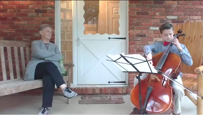 Boy playing cello on front porch next to grandmother
